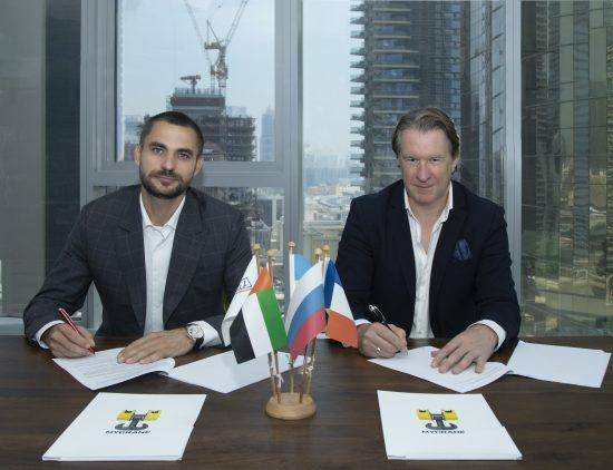MYCRANE founder Andrei Geikalo, left, signs a partnership agreement with new UAE and Oman franchise partner Kirill Vishensky